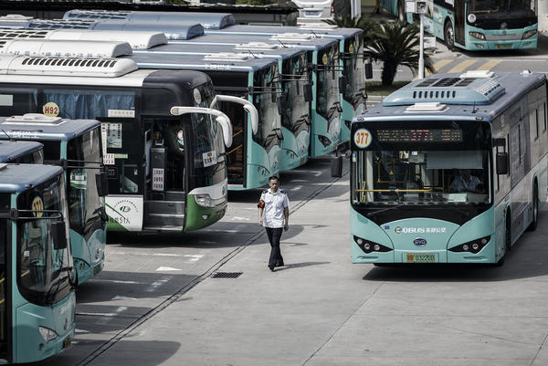 A worker walks past a BYD electric bus at a public transportation hub in Shenzhen.