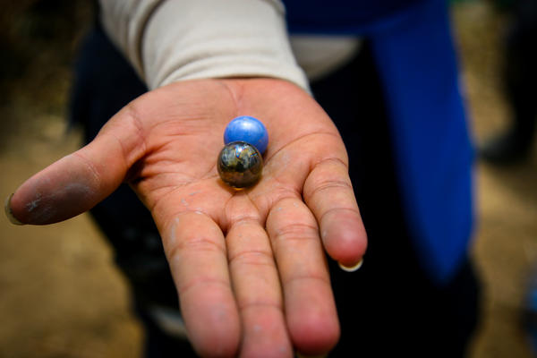 A member of the Handicap International de-mining team shows ball bearings that were found inside a homemade land mine that the team blew up to deactivate it.