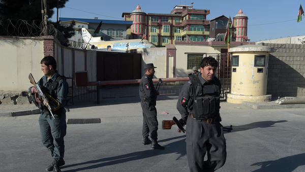 Afghan policemen stand guard near an entrance gate at the Shamshad TV Network after gunmen who were reportedly disguised as policemen stormed the media outlet in Kabul on Tuesday.