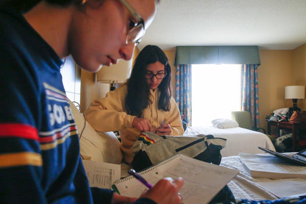 The Roldán sisters do their homework on the bed in the hotel room they share with their mom and stepdad.