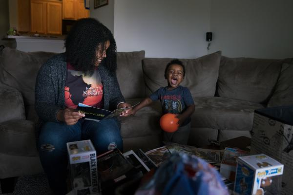 Stephanie Williams and her son Micah, 2, sit on the sofa looking at comic books in their living room in Charlotte, N.C.