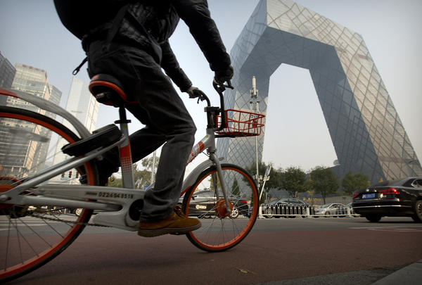 A man rides a Mobike bicycle past the CCTV Headquarters building in Beijing.