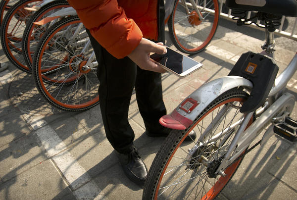 A customer uses a cellphone to scan a QR code, which allows them to unlock one of the shared Mobike bicycles parked in Beijing.