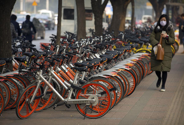 A woman walks past Mobike shared bicycles parked along a street in Beijing.