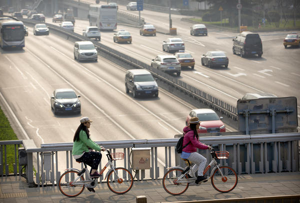 People ride Mobike shared bicycles along an expressway overpass in Beijing.