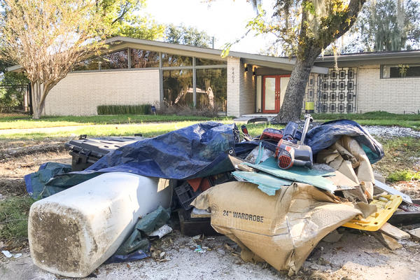 A broken vacuum and other flood-damaged items wait for pickup outside Jimmie Sue Mayes' mid-century rancher in Houston. Mayes is trying to sell her property for essentially the value of the land.