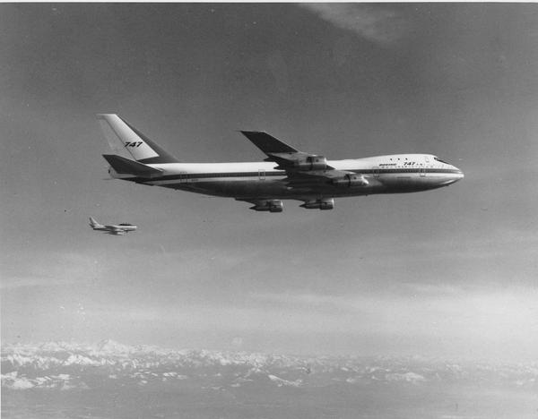 A Boeing model 747, the largest commercial jetliner in the world, flies over the Puget Sound area of western Washington state in October 1969. The 747 jet is accompanied by a Sabre V chase plane, background, to observe certain flight tests. (AP Photo)