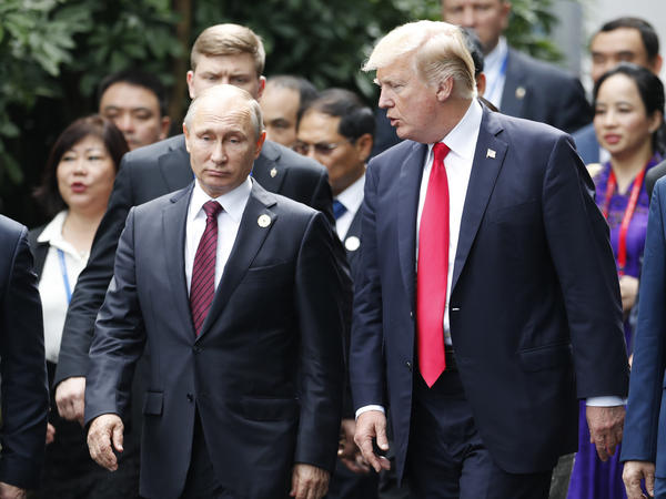President Trump and Russia's President Vladimir Putin talk during the family photo session at the APEC Summit in Danang, Vietnam on Saturday.