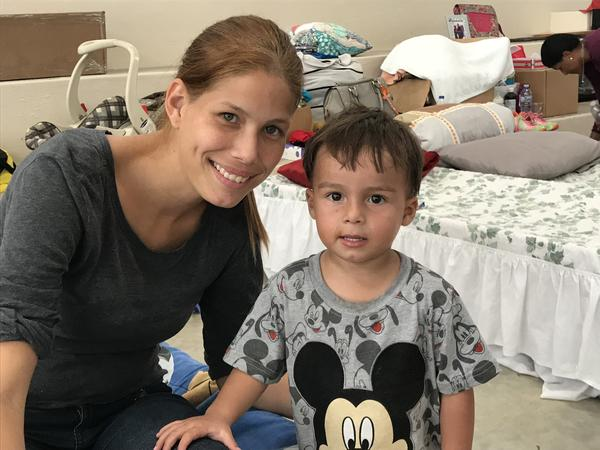 Yamyria Morales and her two children moved into an emergency shelter a few days after Hurricane Maria hit. Morales says she's grateful to have a safe place to sleep, but the noise and lack of privacy at the shelter are taking a toll. She's sitting on the cot she shares with her 2-year-old son Jonael.