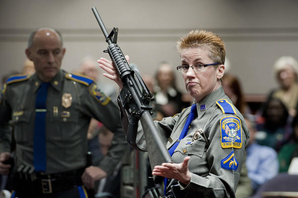 In this Jan. 28, 2013, file photo, firearms training unit Detective Barbara J. Mattson, of the Connecticut State Police, holds up a Bushmaster AR-15 rifle, the same make and model of gun used by Adam Lanza in the Sandy Hook School shooting. (Jessica Hill/AP File)