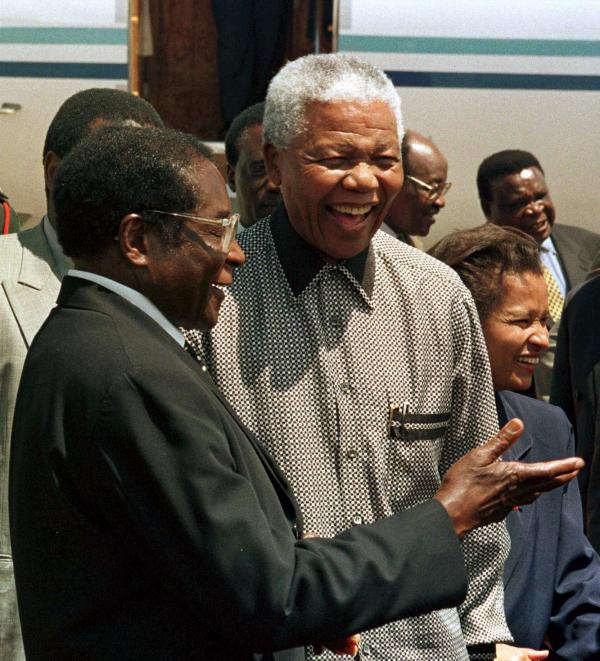 Zimbabwe's President Robert Mugabe (left) greets South African President Nelson Mandela in Harare, Zimbabwe, in 1998. The two men have shaped their countries in dramatically different ways.