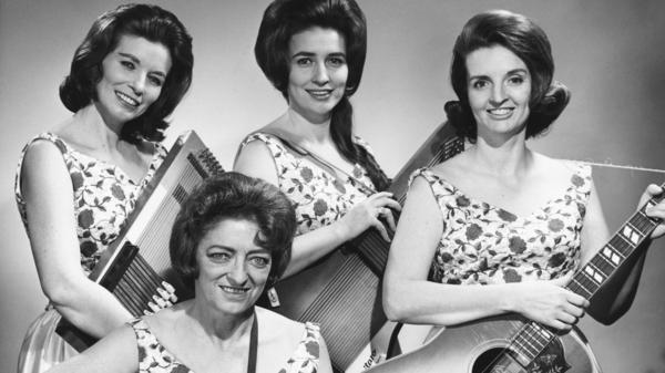 With her family bands, Maybelle Carter — shown here, sitting, with her daughters June, Anita and Helen — helped create the sound of modern country music.