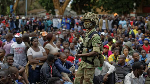 An army soldier stands guard as protesters demanding President Robert Mugabe stand down, gather on the road leading to State House in Harare, Zimbabwe, on Saturday, Nov. 18, 2017.