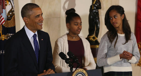 "President Obama's daughters, Sasha, middle, and Malia, right, look on as their father speaks, and jokes, before pardoning ""Cheese"" and his alternate ""Mac"" in 2014 at the White House turkey pardoning."