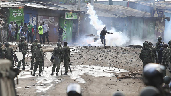 A supporter of opposition leader Raila Odinga throws back a canister of tear gas toward riot police during running battles with police in Kibera Slums in Nairobi, on Sunday.