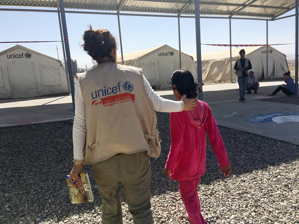 "Kawkab walks with a social worker in the Dabaga camp for displaced Iraqis. Kawkab says she was seven or eight when she saw ISIS militants shoot her mother dead. ""They shot her with an assault rifle,"" she says. ""They shot her and she died and they threw her off the bridge. I asked them, 'Why did you kill her? She's my mother. She didn't do anything.'"""