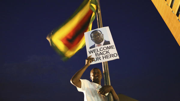 A supporter of Zimbabwe's incoming leader Emmerson Mnangagwa holds his portrait while waiting for him to arrive at the ZANU-PF Headquarters in Harare on Wednesday.