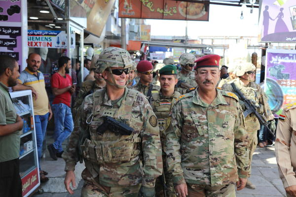U.S. Army Lt. Gen. Paul Funk (left), and Iraqi Maj. Gen. Najm Abdullah al-Jibouri, walk through a busy market in Mosul, Iraq, on Oct. 4. U.S. forces in Iraq, Syria and Afghanistan have been increasing this year under President Trump, going from about 18,000 at the beginning of the year to 26,000 recently, according to Pentagon figures.