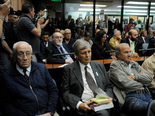 "Front row, left to right: Jorge Eduardo Acosta, ""The Tiger""; Alfredo Astiz, the ""Angel of Death""; pilot Georges Mario Daniel Arru; and Carlos Octavio Capdevilla, known as ""Tommy,"" are seen during their sentencing hearing Wednesday in Buenos Aires."