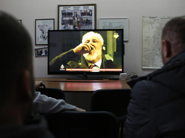 "Bosnian viewers watch as Slobodan Praljak brings a small glass of liquid to his lips at the International Criminal Tribunal for the former Yugoslavia on Wednesday. Praljak, who had just had his 20-year sentence for war crimes upheld, ingested the liquid and declared ""I have just drunk poison."" He died just hours later."