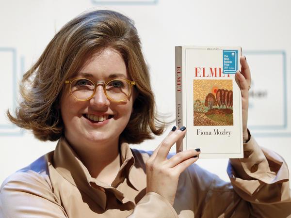 Author Fiona Mozley poses with her book <em>Elmet</em>.