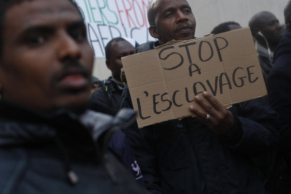 """A protestor holds a placard reading """"Stop slavery"""" as he attends a demonstration against slavery in Libya outside the Lybian Embassy in Paris, Friday, Nov. 24, 2017. Interpol says 40 suspected human traffickers have been arrested and nearly 500 of their victims freed in a vast police operation in five African countries. (AP Photo/Thibault Camus)"""