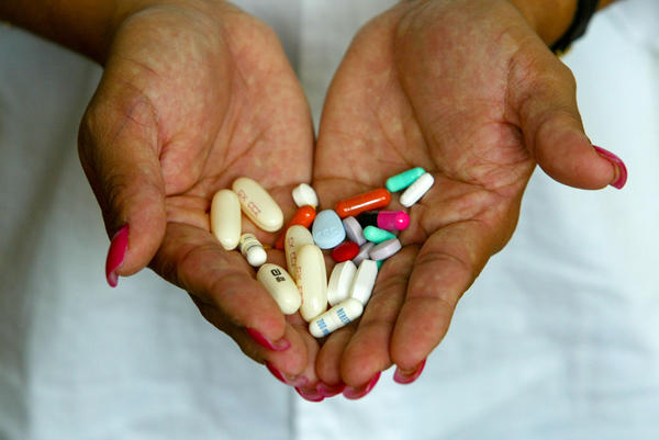 A woman holds the 14 different AIDS medications that she takes three times a day. Antiretroviral drugs have turned HIV from a death sentence into a chronic illness.