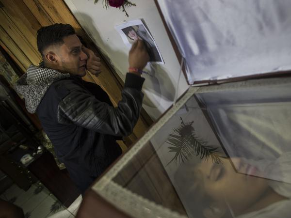Rudy Fonseca, 29, cries next to the coffin containing the remains of his sister Kimberly Dayana Fonseca, 19, in Tegucigalpa, Honduras on Saturday. She was shot by gunmen who witnesses say were police.