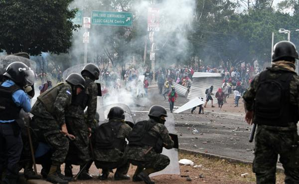 Supporters of Honduran presidential candidate Salvador Nasralla clash with soldiers and riot police near the Electoral Supreme Court (TSE) on Thursday.