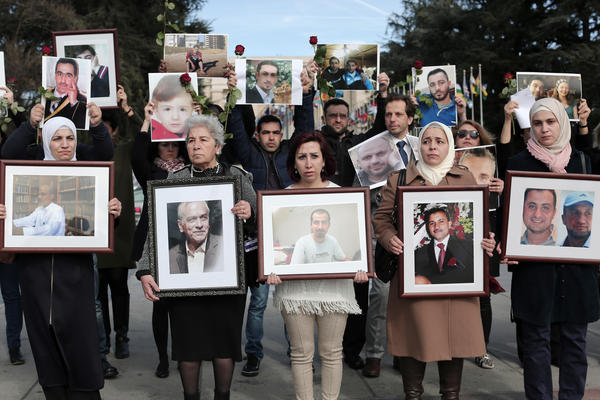 During peace talks in Geneva in February 2017, Syrians hold images of loved ones disappeared by Syrian government forces during more than six years of civil war.