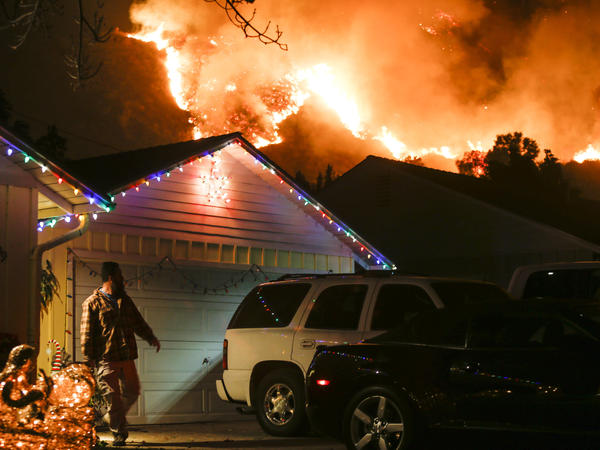 A man prepares to evacuate his home as a wildfire burns along a hillside near homes in Santa Paula, Calif., on Tuesday.