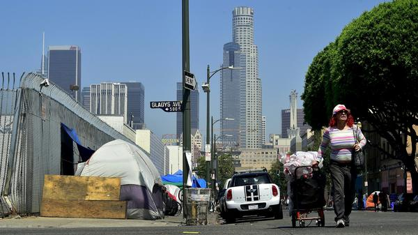 A woman pushes her cart full of belongings along the street past tents on the sidewalk near skid row in downtown Los Angeles in June.