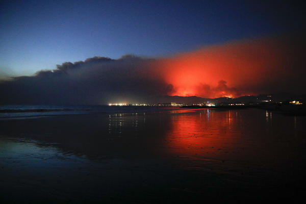 A wildfire continues to burn Tuesday as its red glow is reflected on the beach in Ventura.