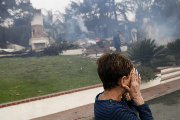 A woman cries as she covers her face near her destroyed home after a wildfire swept through Ventura.