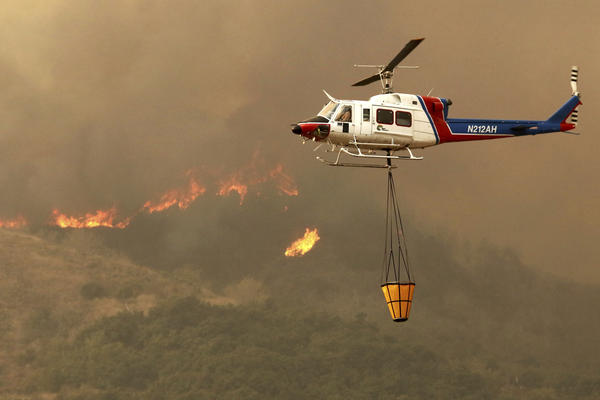 A helicopter makes a water drop on hot spots after the Thomas Fire swept through Ventura.