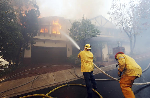 Los Angeles firefighters battle to contain flames to a burning home.