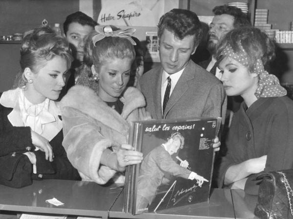 Johnny Hallyday and actress Catherine Deneuve find a copy of Hallyday's<em> Salut les Copains</em> album at a record shop in Paris in 1962.