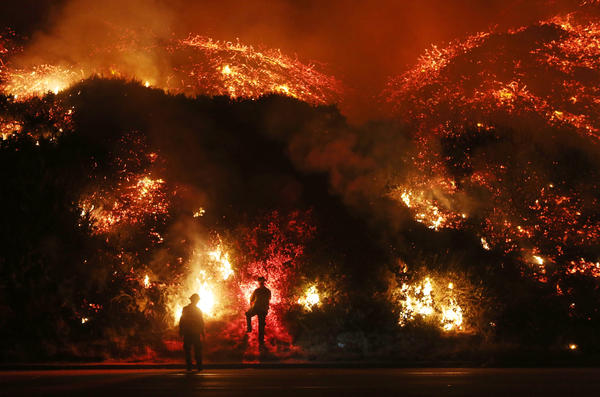 Firefighters monitor a section of the Thomas Fire along the 101 freeway north of Ventura.