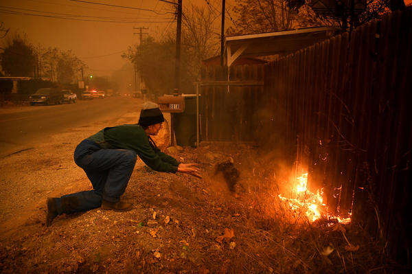 Carolyn Potter throws dirt on her fence along Nye Road in an effort to save her house from the Thomas Fire in Casita Springs on Tuesday.