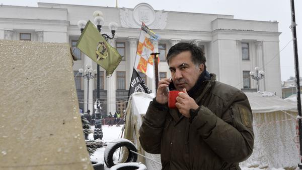 Former Georgian President Mikhail Saakashvili talks on a cellphone at a barricade in front of the Ukrainian Parliament in Kiev, where his supporters are camping.