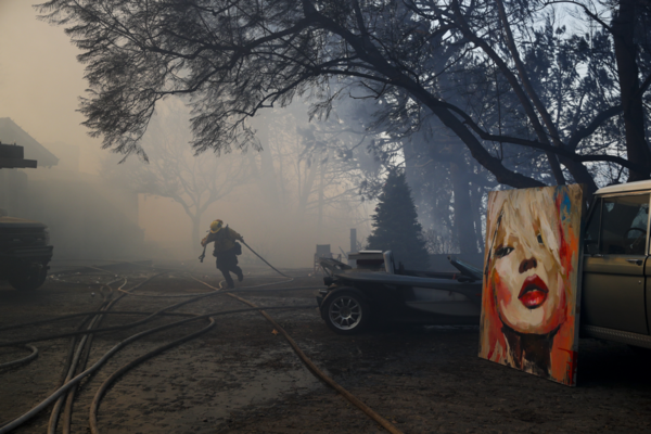 A firefighter carries a water hose as a large painting saved from a wildfire is propped against an SUV in the Bel Air district of Los Angeles.