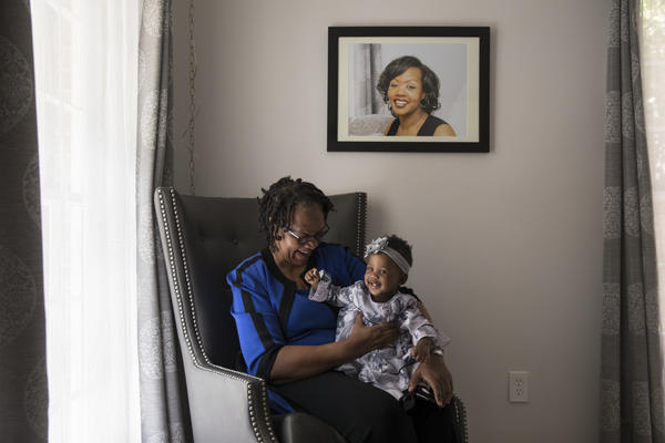 Wanda Irving holds her granddaughter, Soleil, in front of a portrait of Soleil's mother, Shalon, at her home in Sandy Springs, Ga. Wanda is raising Soleil since Shalon died of complications due to hypertension a few weeks after giving birth.