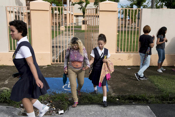 Marianle Vejerano and her eighth-grade daughter, Sonia Marie, leave after participating in a protest in front of Liberata Iraldo. Some teachers, parents and students want the school reopened and are opposed to taking children to classes at the nearby Pedro Falu Orellano High School.