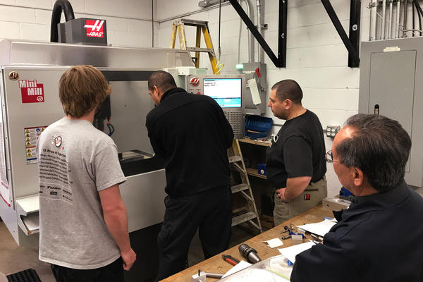 Students enrolled in a training program gather around a computer controlled metal forming machine at the Custom Group. Pasciuto, the company's president, says he and other companies would take advantage of a tax incentive to train more workers.