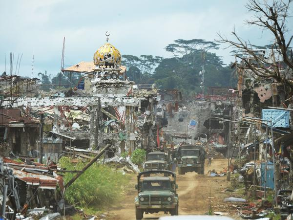 Military trucks drive past destroyed buildings and a mosque in what had been the center of fighting in Marawi on the southern Philippine island of Mindanao on Oct. 25, days after the military declared that the battle against ISIS-linked militants was over.