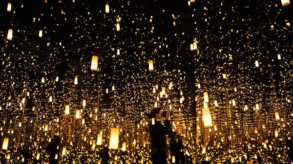"""A woman photographs inside the """"Aftermath of Obliteration of Eternity"""" room during a preview of the Yayoi Kusama's """"Infinity Mirrors"""" exhibit at the Hirshhorn Museum on Feb. 21, 2017 in Washington, D.C."""