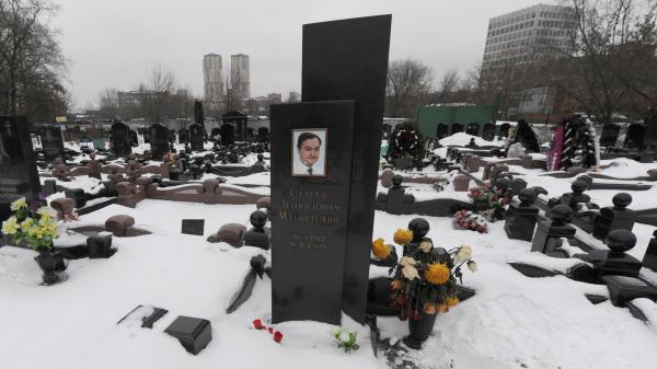 A picture taken on December 7, 2012, shows the snow-clad grave of Russian lawyer Sergei Magnitsky with his portrait on the tomb at a cemetery in Moscow.