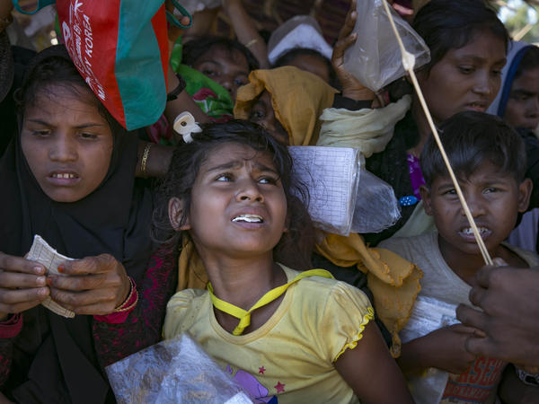 Recently arrived Rohingya refugees queue for relief aid as a man beats back the crowd with bamboo in November in Cox's Bazar, Bangladesh.