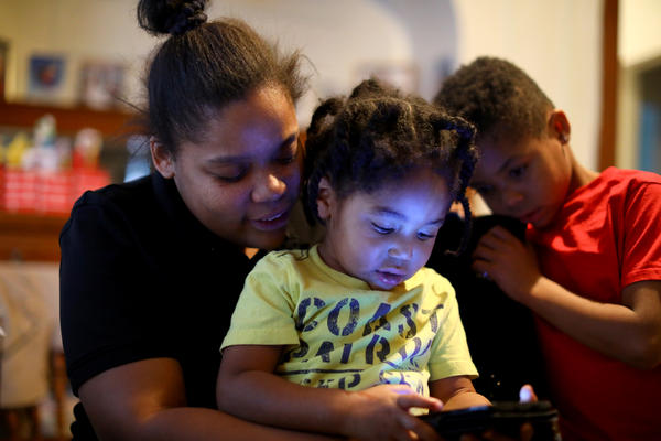 Christine Thompson plays music on her phone for her kids at their rental home in Milwaukee. The family is facing eviction in the next week or two.