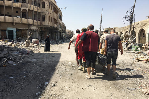 Civil defense workers carrying the body of a civilian retrieved from the rubble of a house destroyed in airstrike. They've collected almost 1,500 bodies so far in west Mosul – many of them women and children – and are still finding casualties.